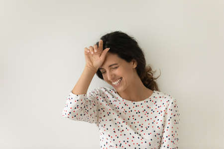 Happy overjoyed beautiful Latin 30s woman laughing out loud, touching face while standing isolated on white background. Cheerful customer expressing joy and having fun. Head shot portrait