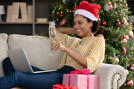 Happy young african ethnic woman in festive red santa hat toasting holding glass of sparkling wine, congratulating with New Year or winter holidays involved in video call conversation using computer.