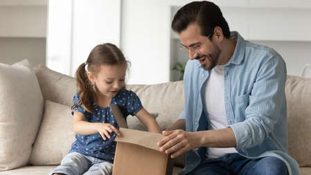 Joyful adorable small child girl opening carton parcel with handsome happy young father at home, feeling excited of fast international delivery shipping, having positive online shopping experience.