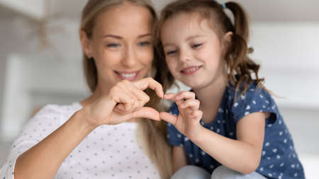Smiling beautiful young mother and little preschool kid daughter showing heart symbol with fingers, tender friendly warm two generations family relations, love and devotion sincere feelings concept.
