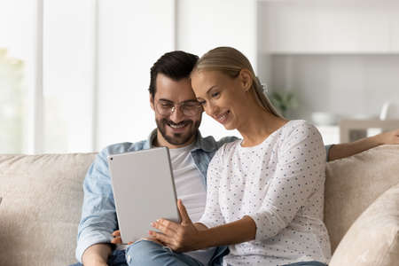 Happy bonding affectionate young family couple using digital computer tablet, holding web camera video call, choosing goods in internet store, web surfing information, planning vacation trip. Фото со стока