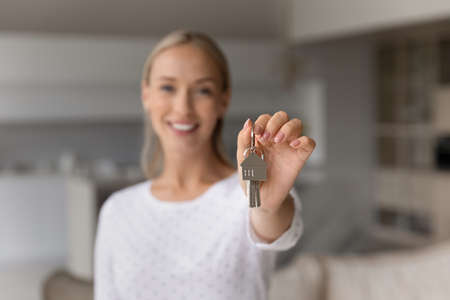 Close up smiling young woman holding keys in hands, celebrating moving into own apartment. Joyful millennial female homeowner feeling excited of purchasing first dwelling, real estate concept.