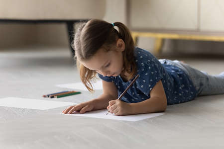 Concentrated happy cute small preschool 6s kid girl lying on warm wooden heated floor, drawing pictures with pencil on paper sheet, enjoying creative hobby pastime activity alone in living room.
