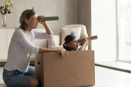 Joyful bonding young mother and little cute kid daughter looking in spyglasses, playing interesting pirates game in modern living room. Happy family having fun, entertaining together at home. Фото со стока