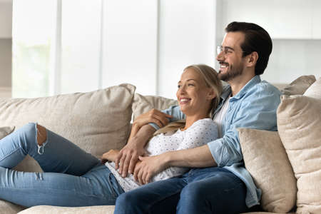 Happy bonding dreamy young family couple resting on cozy sofa, visualizing future looking in distance, planning vacation or enjoying leisure weekend moment together at home, good relations concep.t Фото со стока