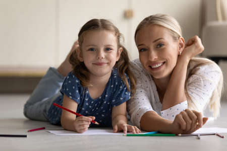 Portrait of smiling bonding little child daughter involved in creative domestic activity with happy young mother, drawing pictures on paper sheet lying together on heated wooden floor at home.