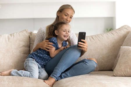 Happy bonding young mother and small cute kid daughter using cellphone, recording funny video for social networks, watching photo content, playing games together at home, online entertainment concept.