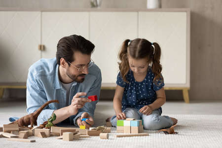 Joyful young father and little cute kid daughter playing wooden toys in modern living room, happy different generations family involved in weekend playful activity, sitting on floor carpet at home.