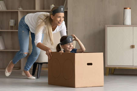 Full length cheerful young mother pushing box with seated small cute kid daughter, playing entertaining pirates game together in living room. Happy family in handmade hats having fun together at home. Фото со стока