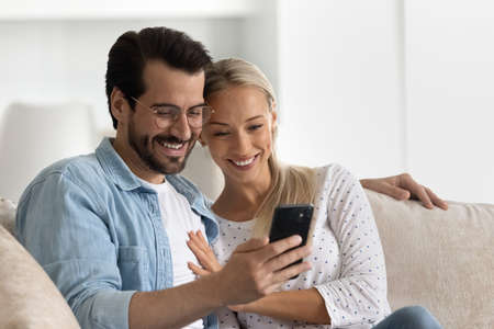 Happy bonding loving married family couple using cellphone, resting on cozy sofa at home. Affectionate young man in eyeglasses cuddling smiling wife, web surfing information or playing games. Фото со стока