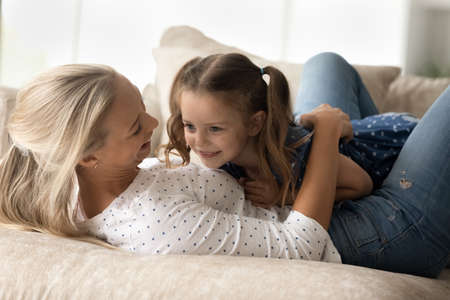 Loving happy young mother cuddling laughing cute little child daughter, playing resting on cozy sofa, joyful two female generations family having fun in living room, entertaining domestic activity. Фото со стока