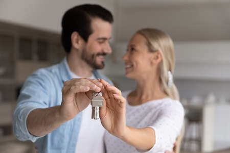 Close up focus on keys in hands of affectionate loving sincere family couple. Happy emotional millennial spouses celebrating moving into own apartments, rental services or real estate concept.
