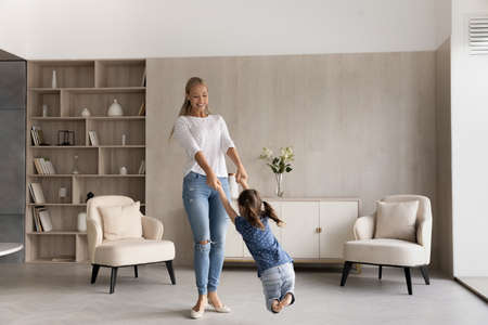 Full length happy beautiful young woman twisting in air cheerful small preschool child daughter, involved in carefree entertaining family activity together in modern living room, carefree pastime. Фото со стока