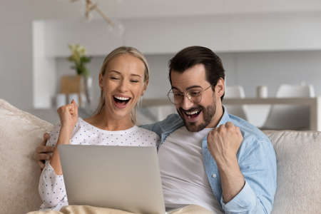 Joyful laughing young married family couple looking at laptop screen, feeling excited of reading amazing online lottery gambling betting auction win, supporting favorite team watching sport match.