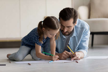 Happy adorable kid girl drawing pictures on paper sheet with caring young father, lying together on heated wooden floor. Smiling bonding different generations family involved in creative activity.