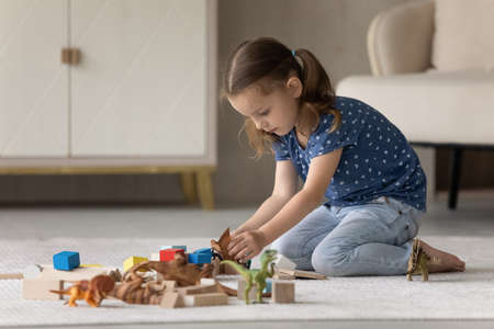 Happy adorable small preschool kid girl playing toys, sitting alone on floor carpet in modern living room. Joyful little 7s child having fun, involved in entertaining playtime activity at home. Фото со стока