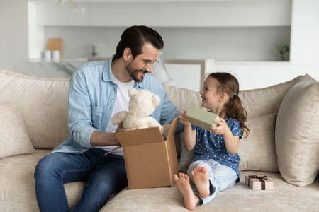 Happy young father unboxing parcel with gifts for small cute kid daughter, sitting together on cozy sofa in living room, satisfied with fast delivery purchase shipment or high quality fluffy toy. Фото со стока
