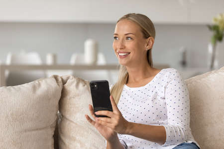 Happy dreamy young beautiful blonde woman using cellphone gadget, enjoying web surfing information, communicating in social network, playing games, thinking of pleasant message or dating invitation.