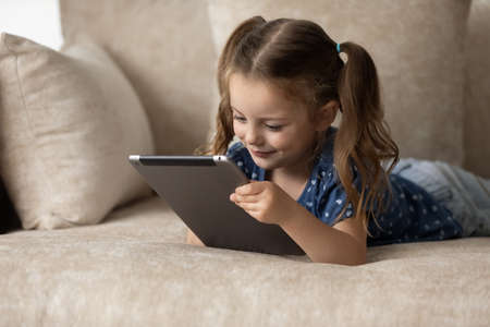 Happy adorable little 6s kid girl lying on comfortable couch with touchpad gadget in hands, involved in playing video games, watching entertaining content in social networks, spending time online.