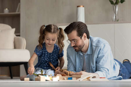Smiling caring young father lying on floor carpet, playing toys with small child daughter, enjoying leisure weekend activity together in living room, happy multigenerational family pastime concept.