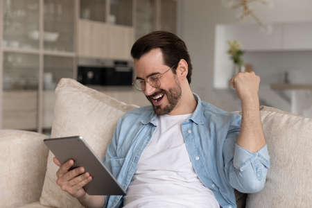 Overjoyed handsome millennial man in eyewear looking at touchpad gadget screen, celebrating online lottery results, feeling excited of getting email with auction betting giveaway win at home.