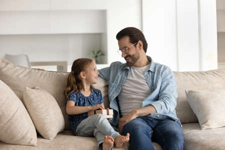 Happy adorable little preschool kid girl holding wrapped gift box, talking with caring young father, resting together on cozy couch, feeling excited with getting birthday present or surprise. Фото со стока