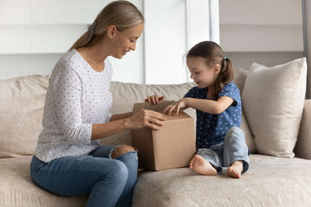 Happy young mother unpacking cardboard box with interested cute little preschool kid daughter, feeling excited of getting parcel with wished purchase item from internet store, online shopping concept. Фото со стока