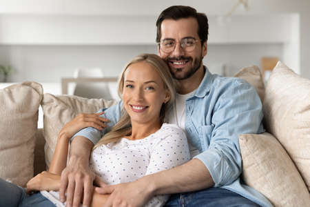 Portrait of smiling beautiful bonding young family couple resting on cozy sofa. Happy affectionate millennial man cuddling beloved woman, looking at camera enjoying carefree leisure moment together.