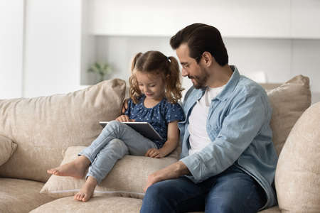 Caring smiling young father in eyeglasses watching happy little preschool kid daughter playing games on digital tablet, resting together on comfortable sofa, parental control, tech addiction concept.