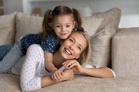 Smiling beautiful young mother holding on back adorable happy preschool small kid daughter, lying together on cozy sofa, spending free leisure weekend time together at home, family pastime concept. Фото со стока