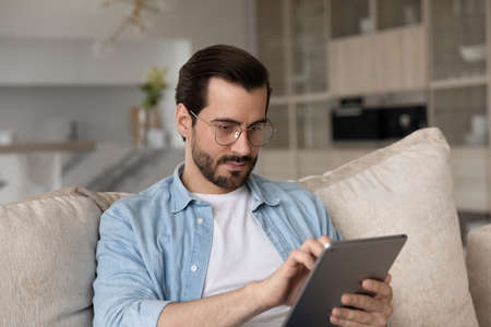Focused millennial generation handsome man in eyeglasses using digital computer tablet, resting on sofa at home. Joyful young male user holding touchpad gadget, web surfing information or playing game