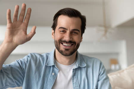 Happy millennial handsome man waving hands looking at camera, starting distant conversation. Smiling friendly young male blogger recording video or steaming stories online, siting on sofa at home.