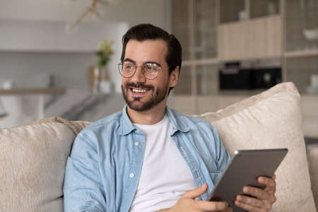 Dreamy happy young man in eyewear looking in distance, holding digital tablet in hands, thinking of pleasant news from email, feeling romantic communicating in social networks, resting indoors.