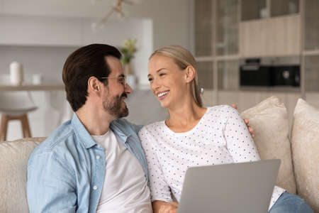 Laughing sincere young married family couple talking, using computer at home. Affectionate happy millennial man and woman resting, watching funny comedian movie film online on laptop, resting on couch