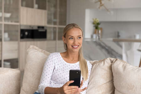 Dreamy beautiful young blonde woman holding smartphone in hands, getting message or email with pleasant news, communicating in social network resting on comfortable couch on weekend at home. Фото со стока