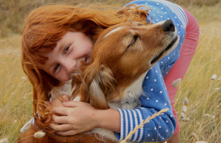 headed: red headed girl hugging red haired dog  Stock Photo