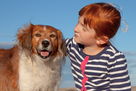 unleashed: red headed girl hugging red haired dog  Stock Photo