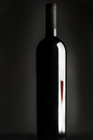 Bottle of wine, reflection of wine glass, red wine, black background Banco de Imagens