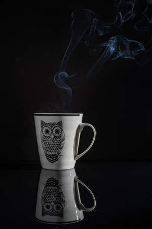 Coffee cup with its reflection with black background. Smoke comes out of the mug. The mug has the image of an owl