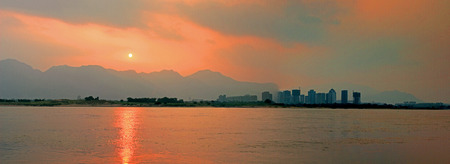 irradiation: At dusk, sunset, twilight mapped on the river, sunset shiny red sky, beautiful scenery.