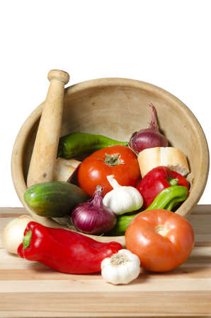 vegetables in mortar kitchen over white background, ingredients for vegetable soup photo