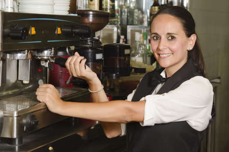 A waitress doing a coffee in a cafe.  photo