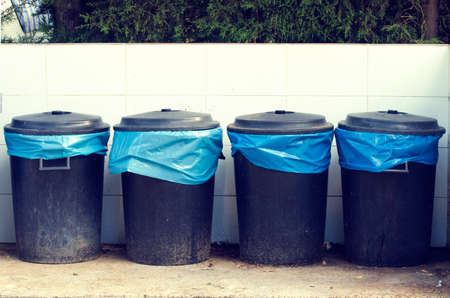 Four bins on the street with garbage bag, made of black Talked