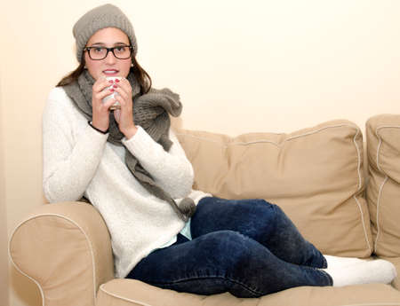 Pretty woman sitting on sofa while drinking from a cup photo