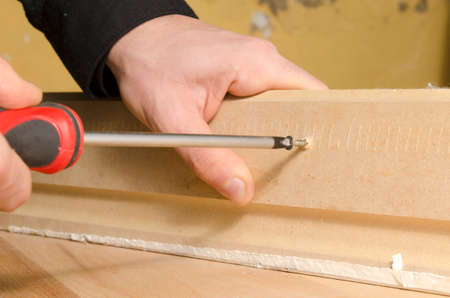 Carpenter using a screwdriver to put a screw into wood photo
