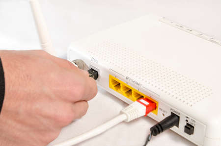 elective: closeup of a hand connecting a modem for high speed internet