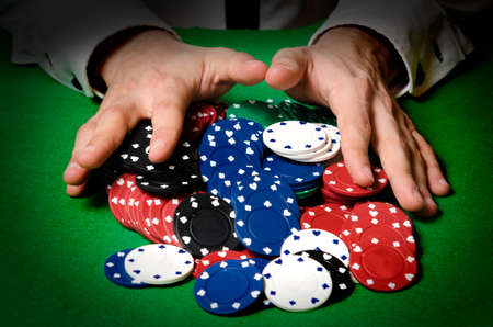 Hands in foreground betting chips in a casino photo