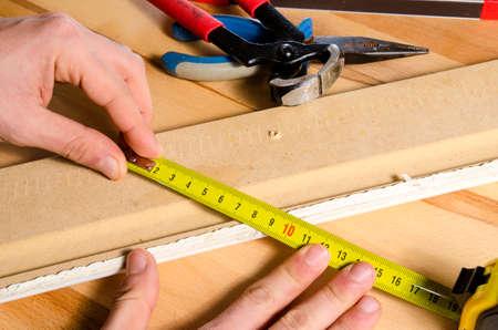 muebles de madera: Detalle de las manos Carpintero que usa un metro