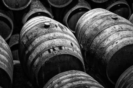 wine barrels stacked in winery in white and black 版權商用圖片