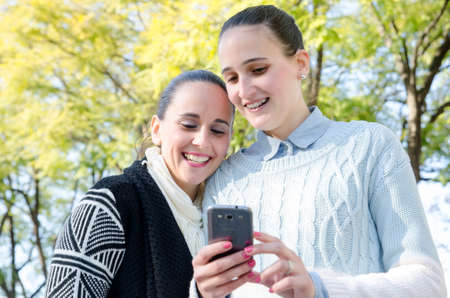 two women using a cell phone and smiling photo